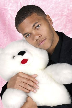 African American man cuddles with his large, white teddy bear during Valentines. photo