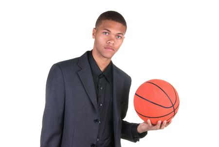 An African American basketball player holding a basketball while wearing his business casual suit Stock Photo - 4864086