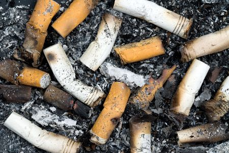 unhealthy living: Cigarette butts and ashes from an ash tray