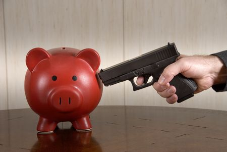 stickup: A man ready to take out his broke piggy bank with a loaded pistol. Stock Photo