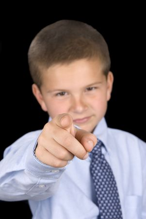 A young boy dressed up in a shirt and tie pointing at the camera, communicating his message to you.  Image was shot using a black backdrop and is not a cutout.  Focus is on index finger. photo