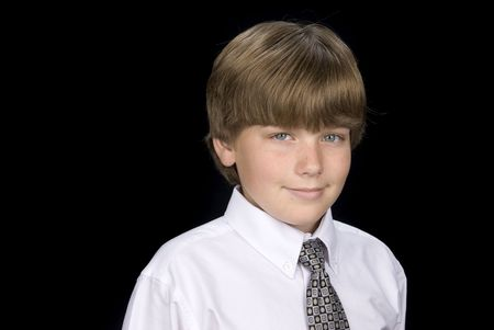 A young boy dressed in a shirt and tie has his portrait taken.  Isolated on a black backdrop. Stock Photo - 4864146