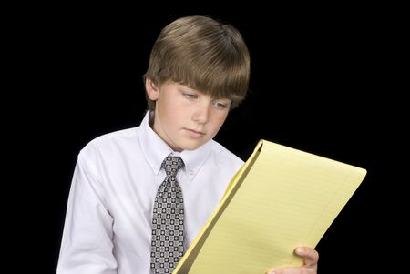 A young boy in formal business dress reads his notepad.  Image was shot against a black backdrop and can be used for any concepts and business inferences. Stock Photo - 4864098