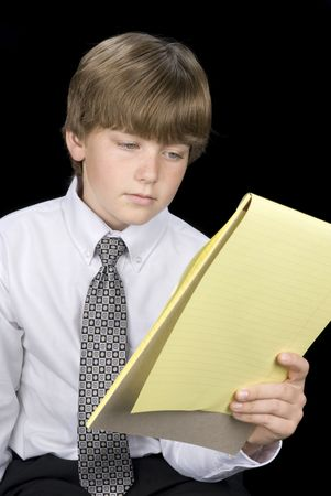 inferences: A young boy in formal business dress reads his notepad.  Image was shot against a black backdrop and can be used for any concepts and business inferences.