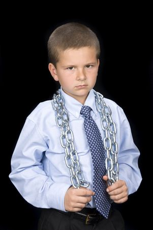 A young boy in a dress shirt and necktie has a chain around his shoulders and a seus look on his face.  Can be used for any business inference. Stock Photo - 4864211