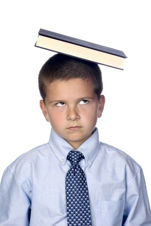A young boy in a dress shirt and tie balances a book on top of his head. photo