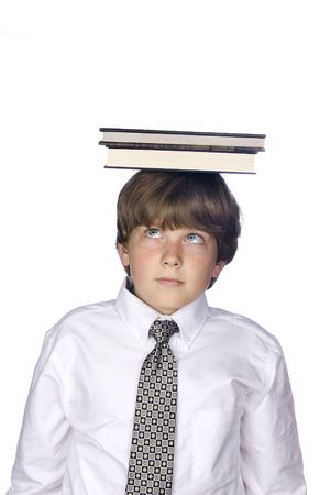 A young boy in a dress shirt and tie balances a book on top of his head.