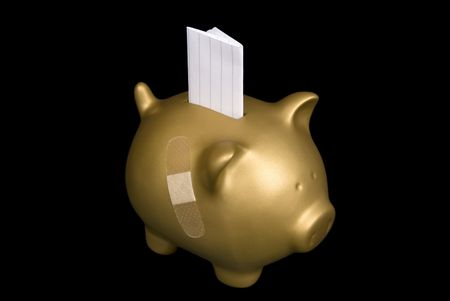 A gold piggy bank wounded by the economy witha copy space slip going insiude.  Buyer can insert anything on the white paper such as IOU, 401K and more debt. photo