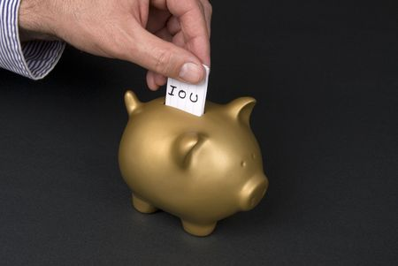 inference: A man places a slip of paper into a piggy bank inferring that he is borrowing from his piggy bank andowes money via an IOU slip. Good image for a retirement financial inference.