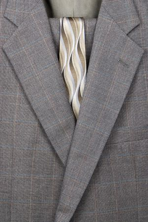 A close up of a business suit and necktie hanging on a hanger. Фото со стока