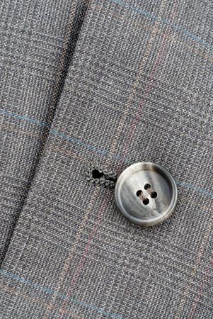 A button on a business suit shows the fine tailoring detail.