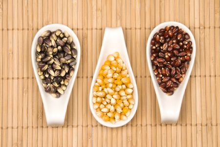 Three types of popcorn including crimson red, black Jewell and classic yellow sit in spoonfulls on a bamboo place mat.