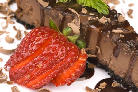 A close up a slice of chocolate cheesecake with a fresh strawberry garnish photo