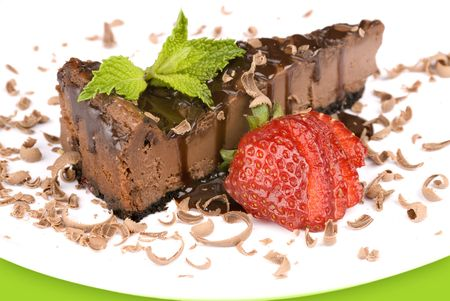 A close up a slice of chocolate cheesecake with a fresh strawberry garnish and mint leaf Stock Photo - 5231678