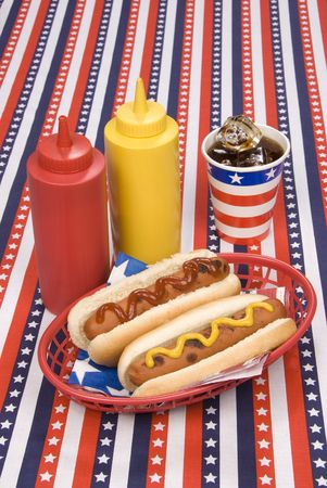fourth of july: A picnic table with a patriotic table cloth hosts a basket of hotdogs with ketchup and mustard bottles and a cold soday.