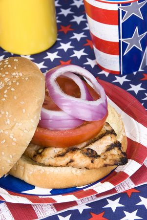 A freshly barbecued chicken burger during a fourth of July\ picnic.