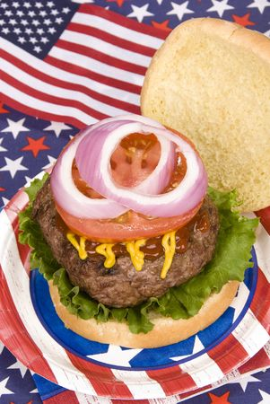 A juicy hamburger with tomoato, onion, mustard and ketchup with a fourth of July patriotic theme Banco de Imagens