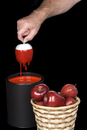 Conceptual image of a man dipping white apples into red paint to form edible red apples in a basket. photo