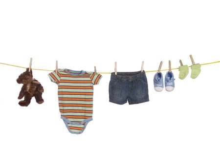 A clothesline used to dry infant clothing including shoes, socks, shirt, shorts and a teddy bear isolated on a white background. Image was shot against a lighted white backdrop and is not a cutout. photo