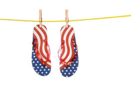 A pair of patriotic Fourth of July flip flops hanging on a clothes line isolated on a white background. Image was shot against a lighted white backdrop and is not a cutout. Stock Photo - 5231552