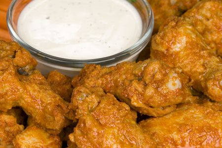 A close up of crisp; spicy chicken wings, also known as hot wings, with ranch dipping sauce.