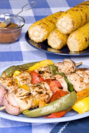 kebob: A barbecued chicken kebab dinner with corn on the cob on a picnic table setting.