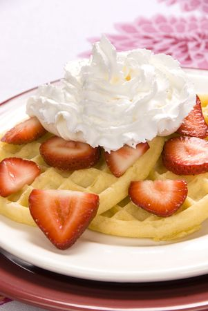 A plate of strawberry waffles with sweet whipped cream. photo