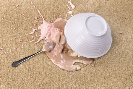 A bowl of spilled Neopolitan ice cream on white carpet that is melting.