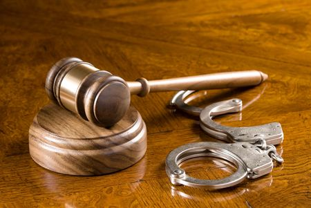 A gavel and block on a richly colored cherry wooden desk with handcuffs.