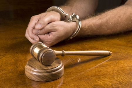 restraints: A man arrested awaits the judge to use his gavel to render a decision. Stock Photo