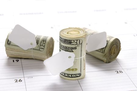 bankroll: Cash money rolls on a desk calendar with blank tags for copy Stock Photo