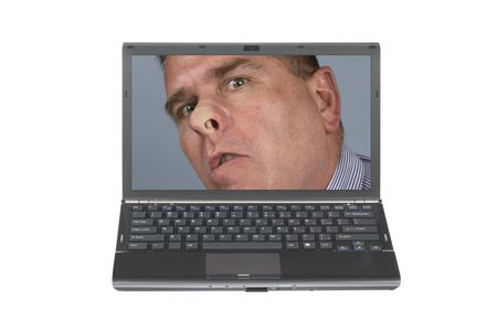 A nosey man pressed his face against a laptop screen being nosey and meddlesome.  Image was shot against a lighted white background and is not a cutout.