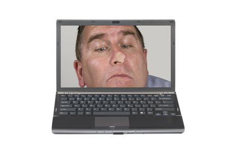 nosey: A nosey man pressed his face against a laptop screen being nosey and meddlesome.  Image was shot against a lighted white background and is not a cutout.