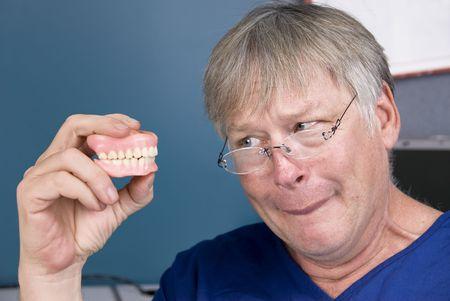 dentadura postiza: Un hombre mira fijamente a sus pr�tesis antes de llevarlos a su boca.
