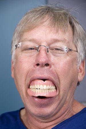 falso: Un hombre muestra su dentadura postiza (dentadura postiza), que muestra lo que sucede cuando usted no tiene una buena higiene dental.