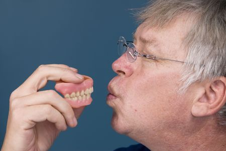 A man kisses his dentures in thanks for allowing him to chew. Stock Photo - 5529915