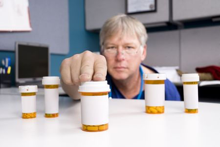 A pharmacist selects the right medication for his patient.  Labels are blank to allow for copy to be placed on the pill bottles. Stock Photo - 5529884