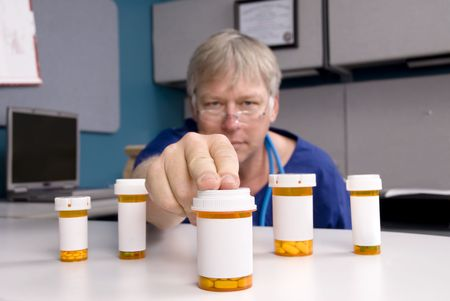 A doctor selects a medication for his customer.  Labels are blank to allow for copy to be placed on the pill bottles. Stock Photo - 5529859