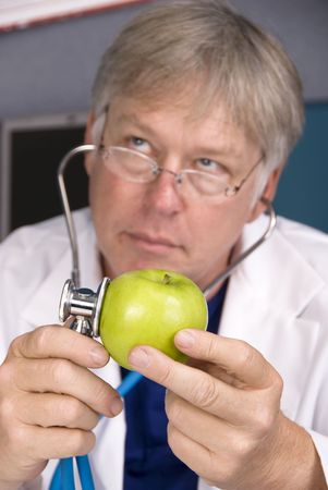 inferences: A doctor examines an apple with his stethoscope.  Good image for healthy eating and diet inferences.