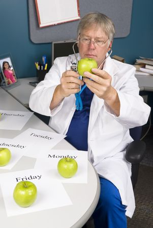 A doctor examines an apple with his stethoscope.  Image is useful for any healthy diet or eating inference. Stock Photo - 5529869