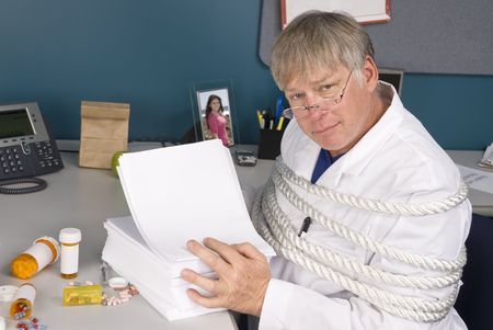 A physician is tied up with a load of bureaucratic paperwork preventing him from doing his job.  Perfect inference for health care reform. Stock Photo - 5529873