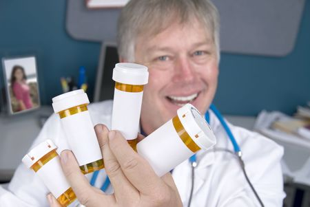 A pharmacist displays pill bottles of medication.  Labels are left blank for copy. photo