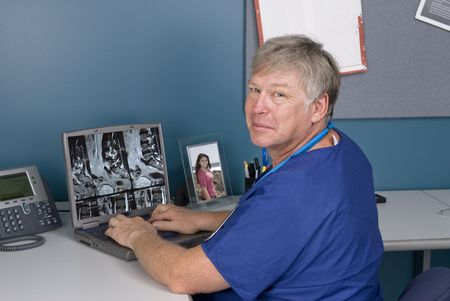 A doctor reviews an MRI on his laptop.  Good for using technology to review imagery as opposed to hard film MRI's. Stock Photo - 5529871