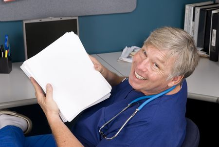 A doctor smailes as he displays a rather large document he must read and understand.  Perfect for any healthcare reform inference.  Copy space is provided oon the paper. Stock Photo - 5529914