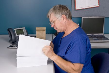 A doctor reviews a large, overwhelming document.  Good for health care reform bill inferences. Paper left blank for placement of copy. Stock Photo - 5529883