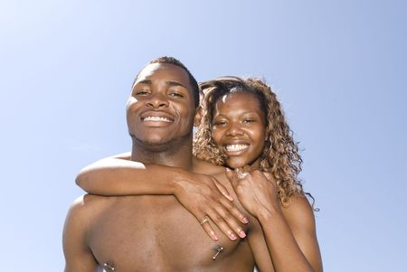 friendliness: An embracing African American couple standing outdoors on a hot, sunny day.