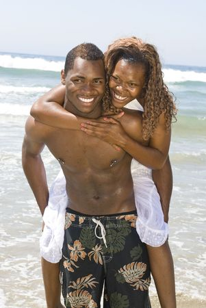 A happy, African American couple in a loving embrace as the husband carries his wife out of the water at the beach. photo