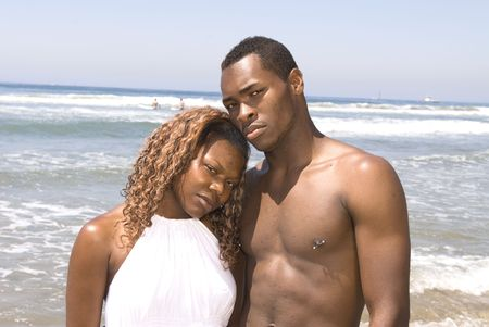 A married African American couple embracing at the beach with a serious expression photo