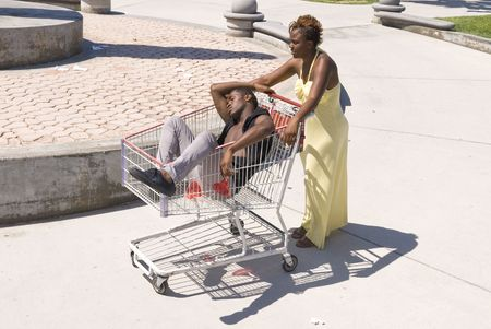 inferences: A woman pushes her passed out husband down a walkway in a shopping cart.  Can be used for partying inferences or alcohol inferences. Stock Photo