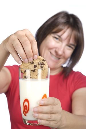 inferences: A woman happily dunks her chocolate chip cookie into a cold gl;ass of milk.  Good image for snacking inferences for adult age groups and unhealthy eating concepts.